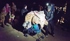 A man and his wife use a stroller to carry essential possessions across the border at night.