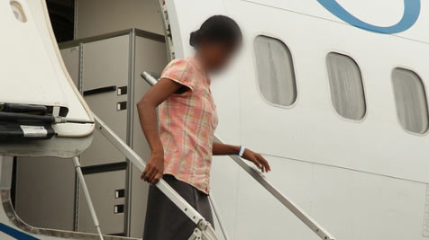 Woman exiting plane in Manus Island